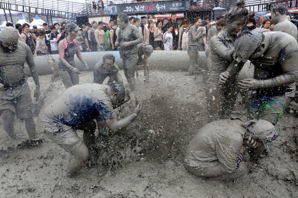 Festivalgoers playing in a pit of mud
