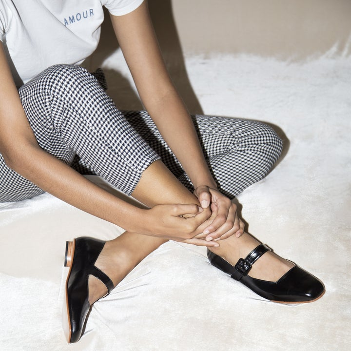 a model wearing a white t-shirt, gingham pants, and the black Mary Jane flats