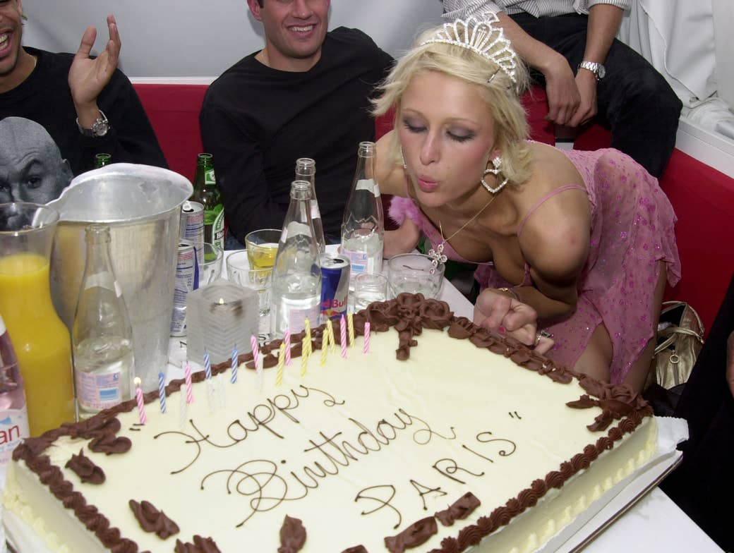 Paris  Hilton blowing out the candles on a birthday cake