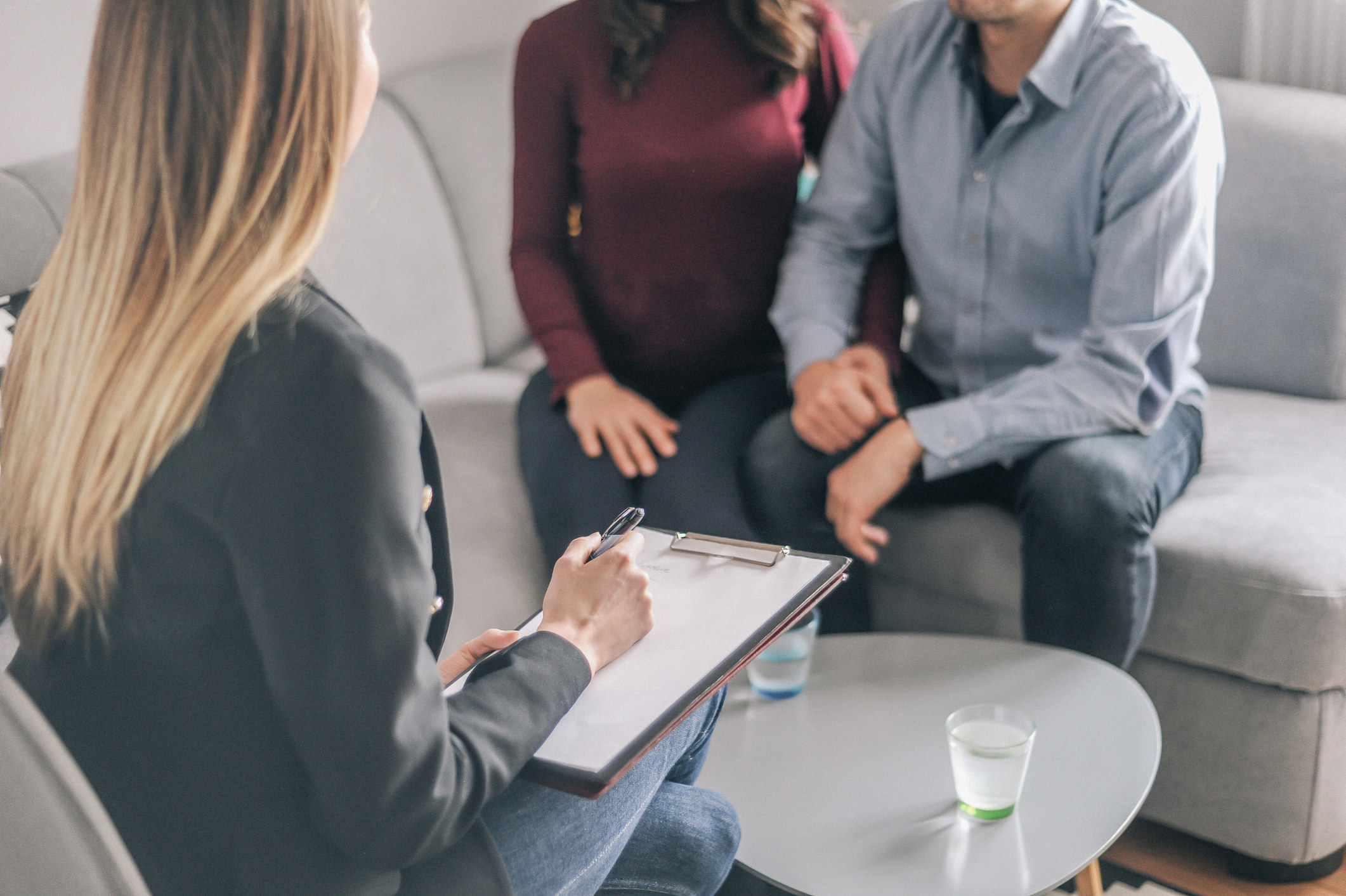 A therapist talks to a couple during a session