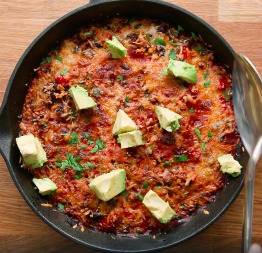 A cast-iron skillet filled with the enchilada rice, which is topped with sliced avocado