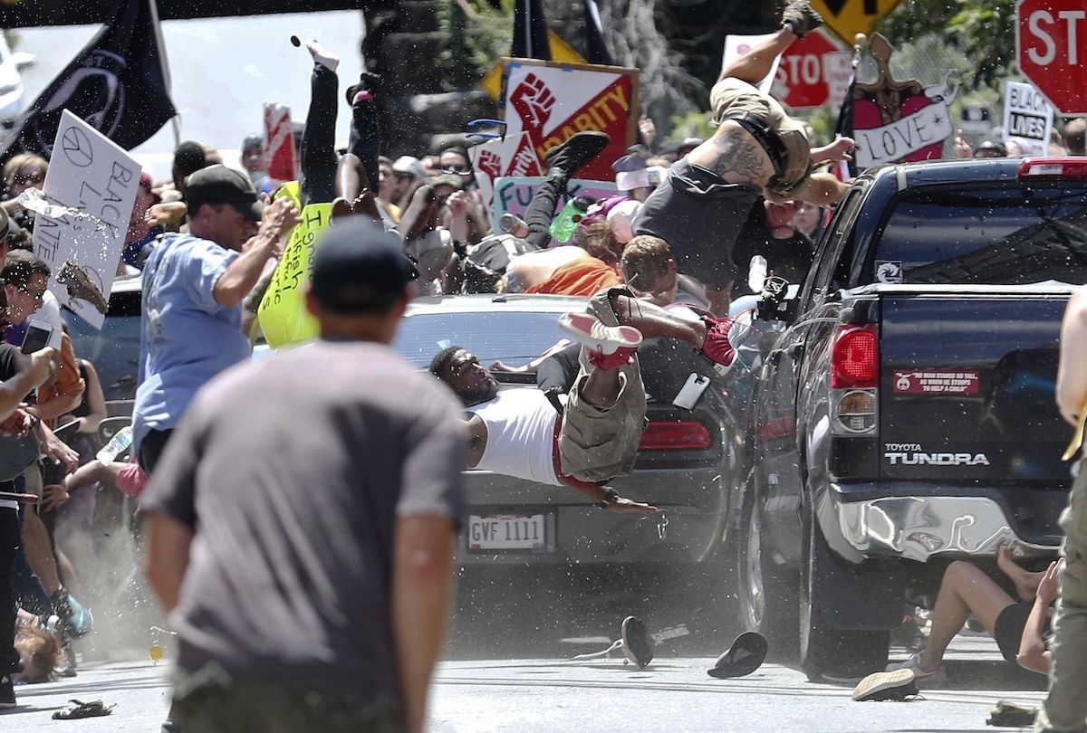 A car drives into a crowd of protesters waving signs as bodies tumble off it