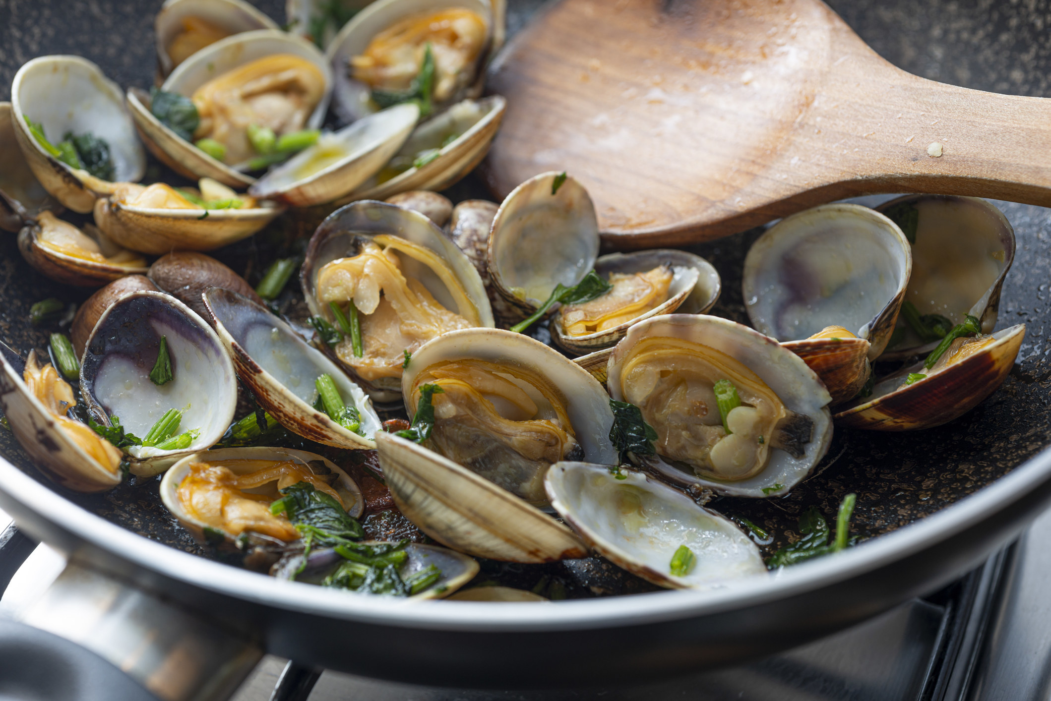 Clams tossed in fresh herbs in a skillet.