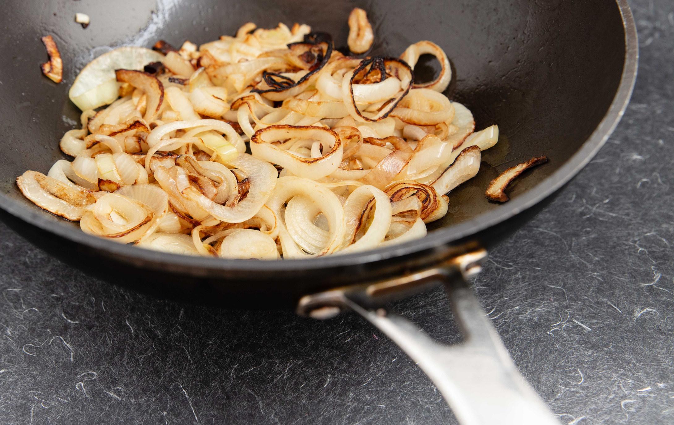 Onion sautéeing in a pan.