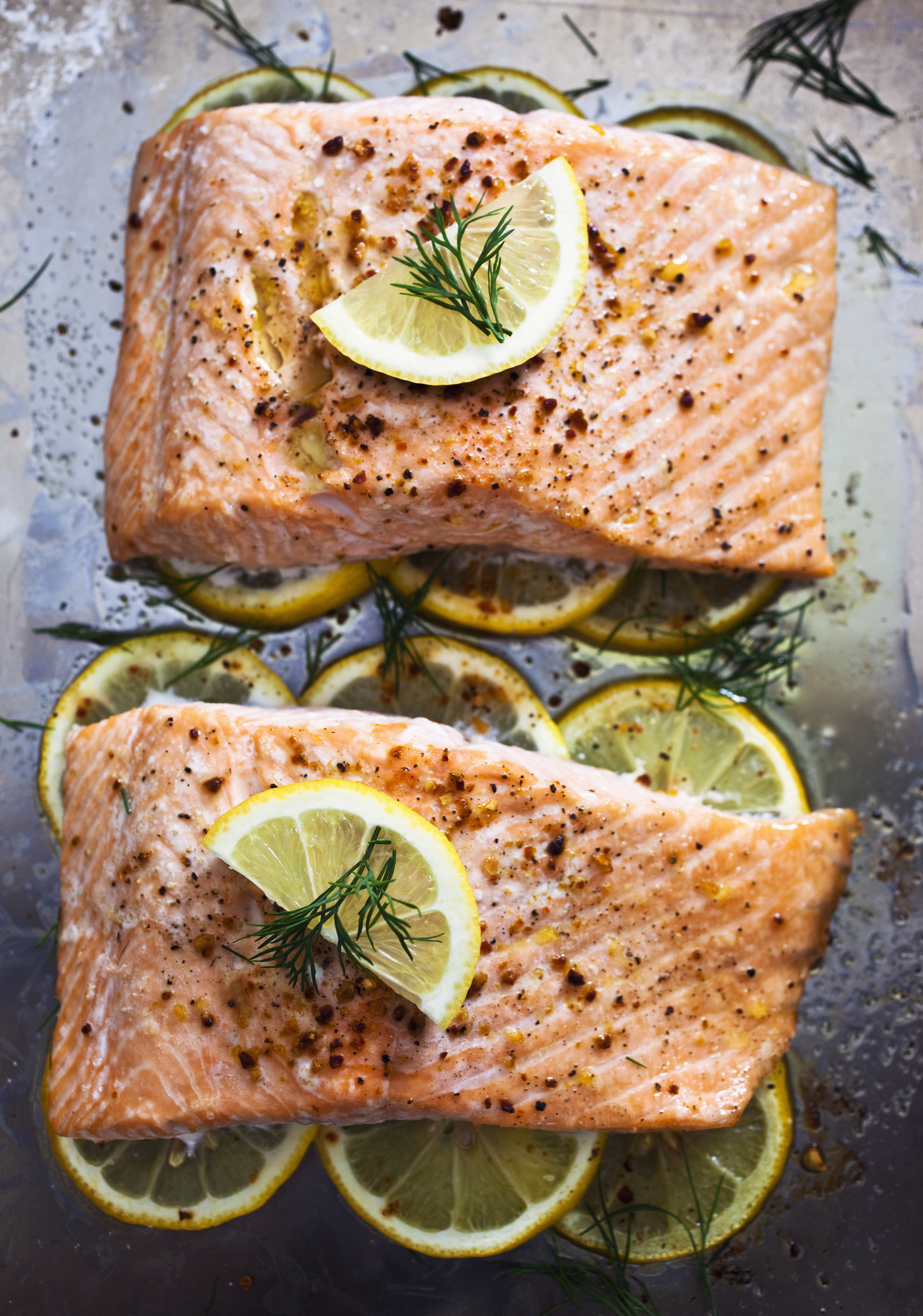 Two pieces of roast salmon over sliced lemon.