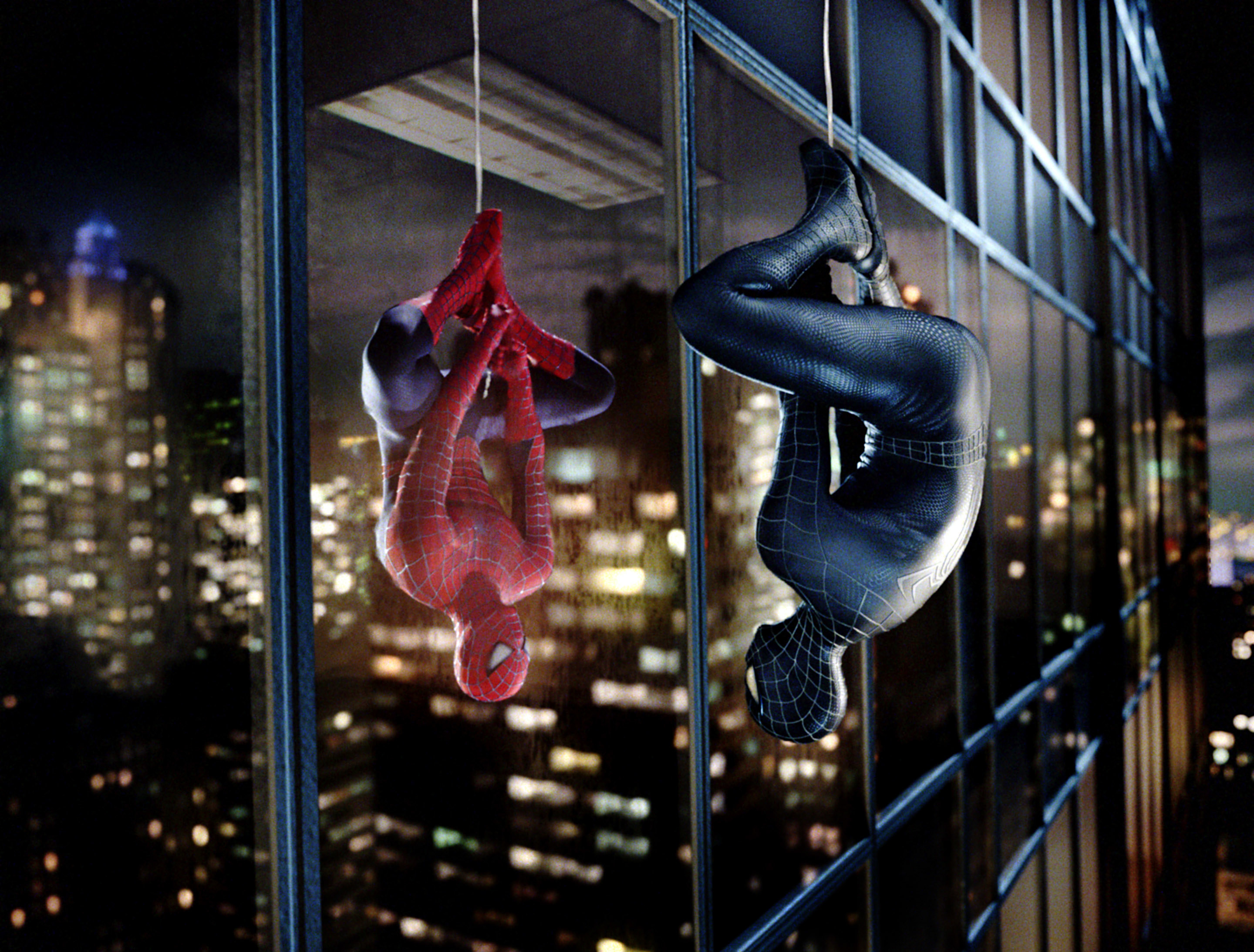 Photo of Spider-Man and Venom hanging upside down and looking at each other through a building window