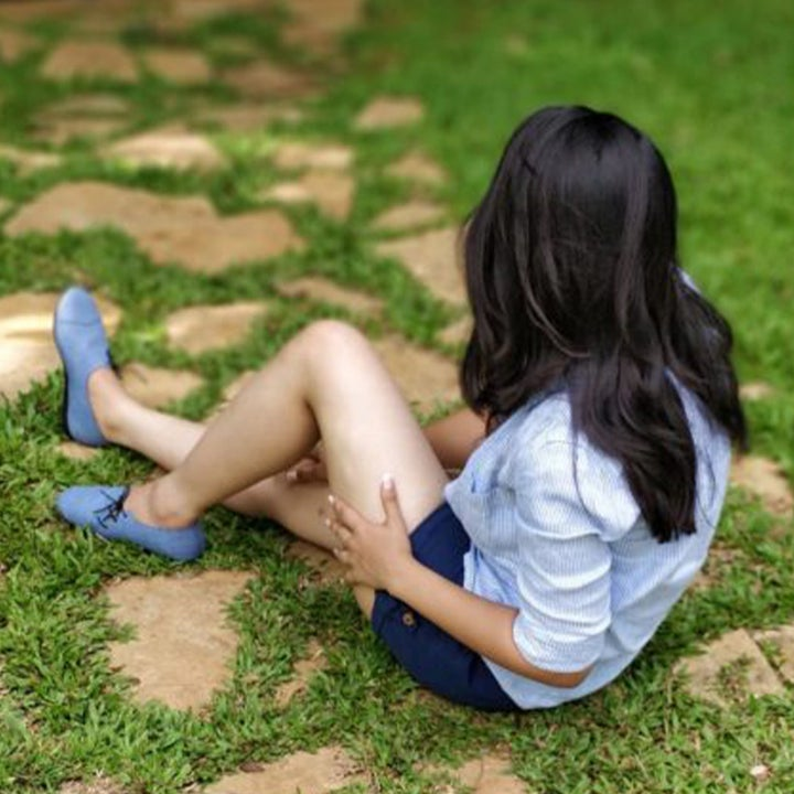 a model sitting in the grass wearing shorts, a shirt and the chambray blue lace-up shoes