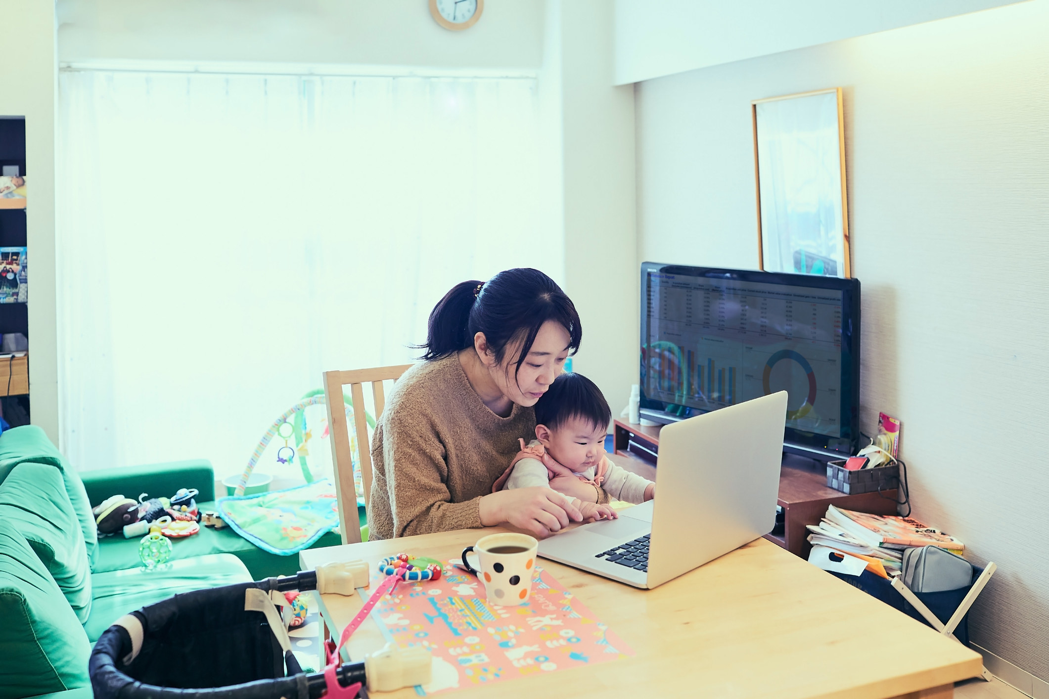 A mom holds her baby as she works on her computer