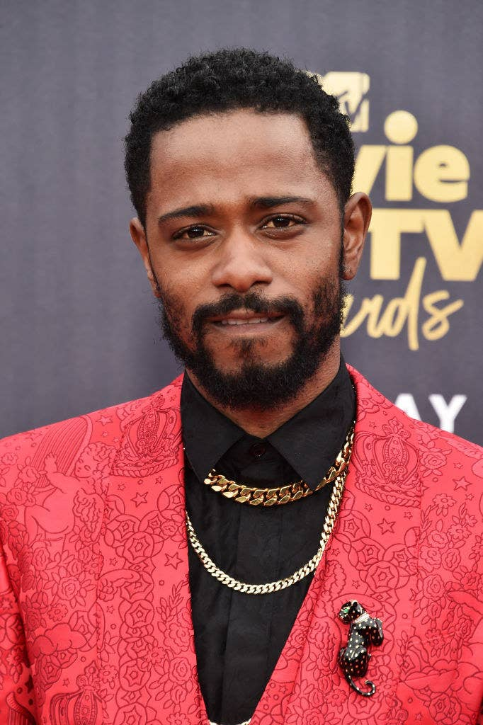 Lakeith Stanfield attends the 2018 MTV Movie And TV Awards a patterned suit and chains