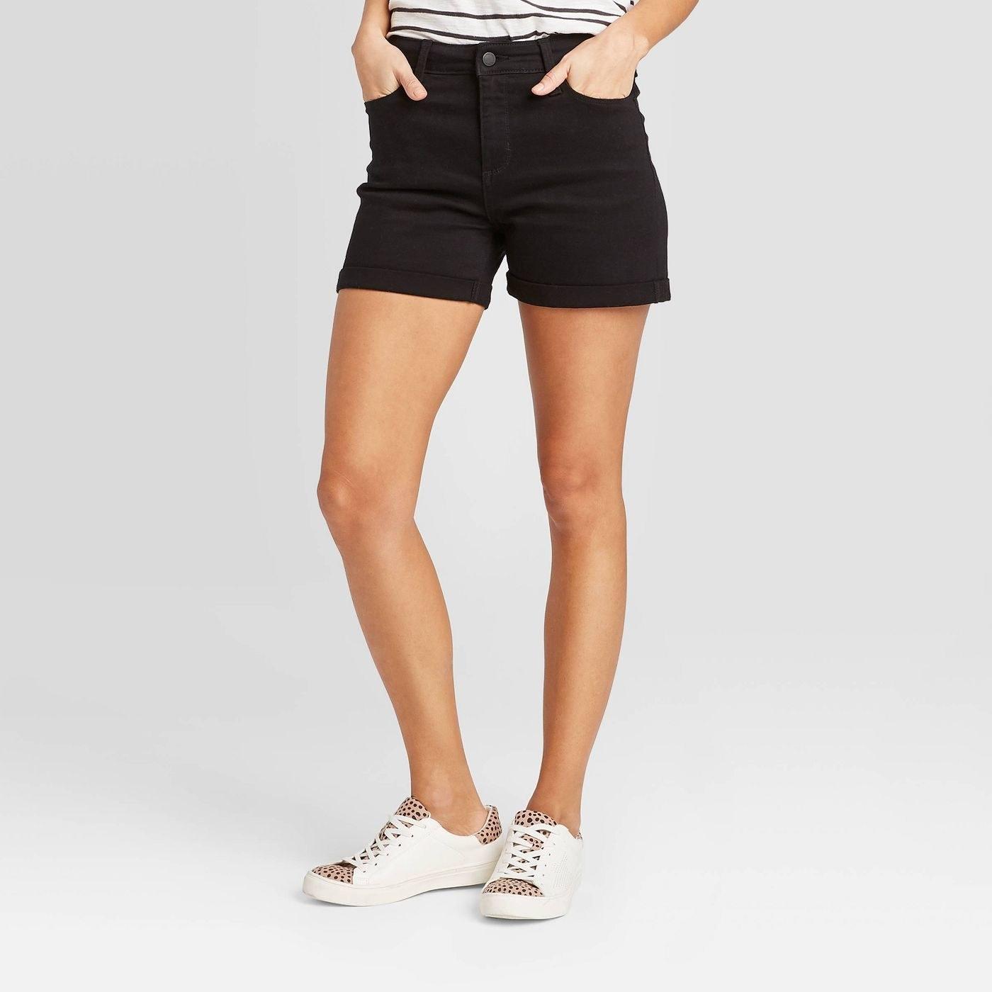 Model in black jean shorts