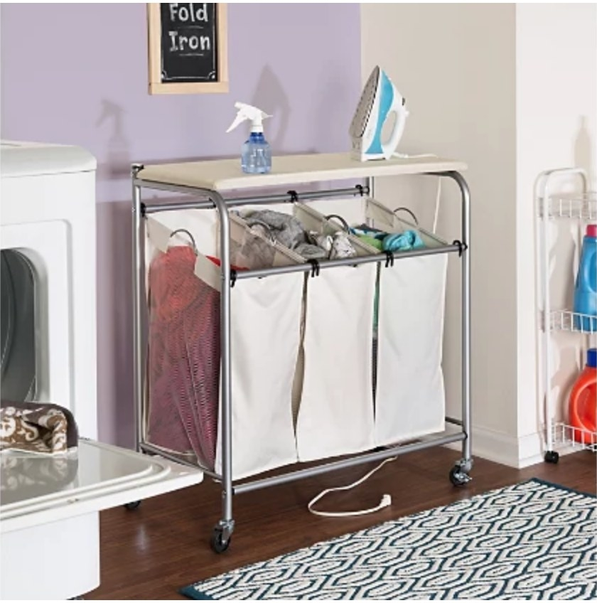 A triple laundry sorter with an attached ironing board