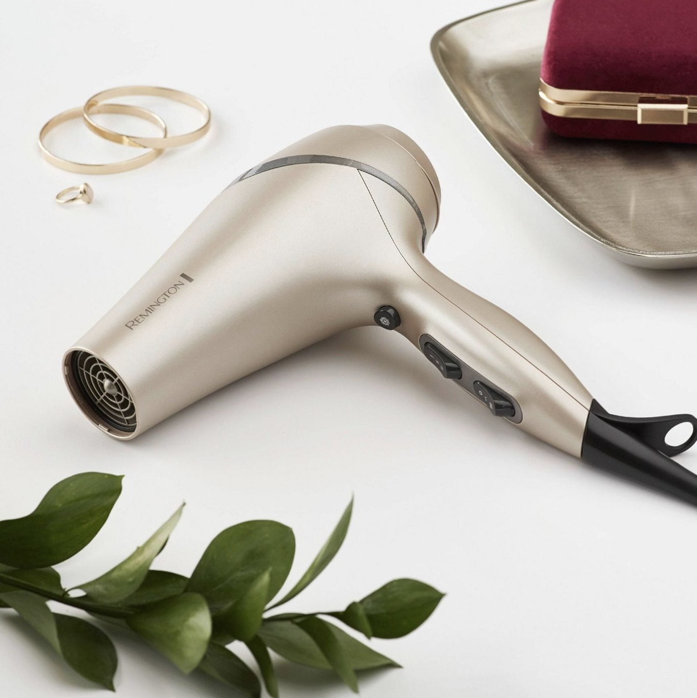 A grey blow dryer with jewelry in the background