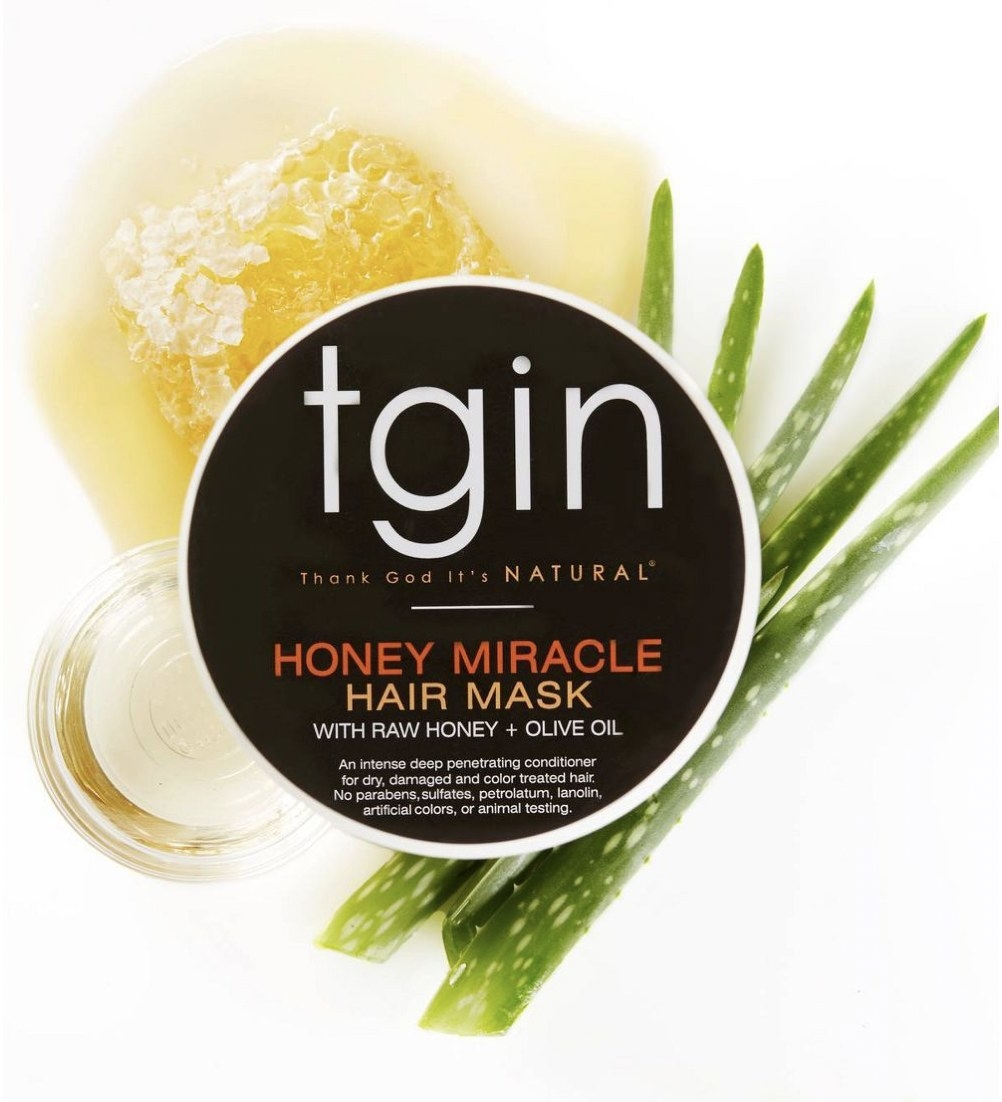 A jar of honey hair mask with aloe vera leaves in the background