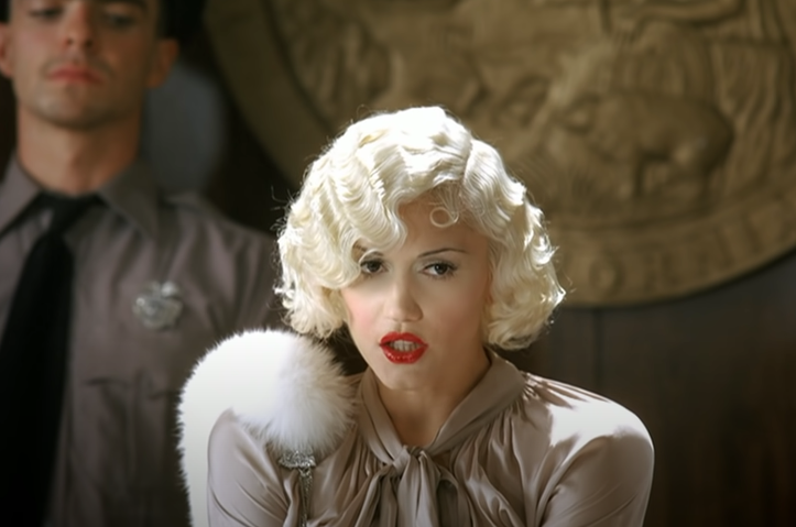 A photo of Gwen Stefani dressed as 1920s movie star taking the stand in a courtroom