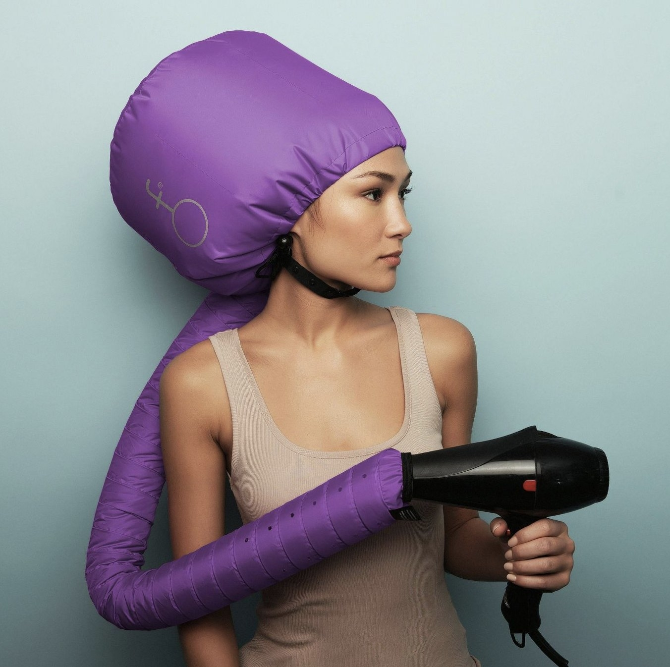 A woman with a purple hooded hair dryer with a blow-dryer attached at the end