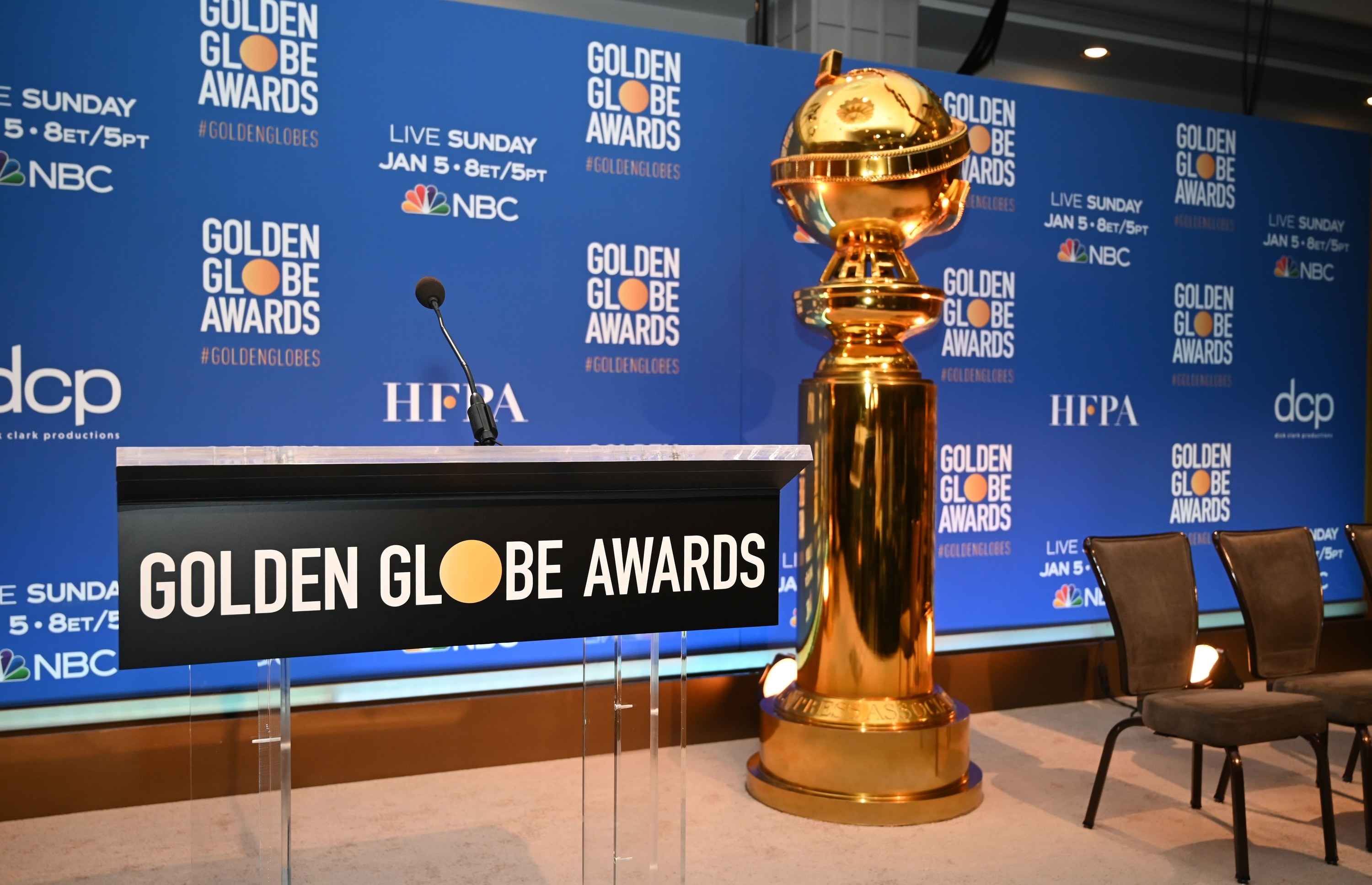 A large-sized Golden Globes trophy next to a podium