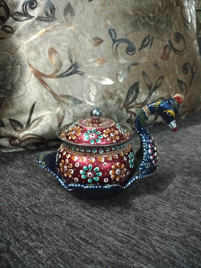 A peacock storage bowl kept on a grey surface