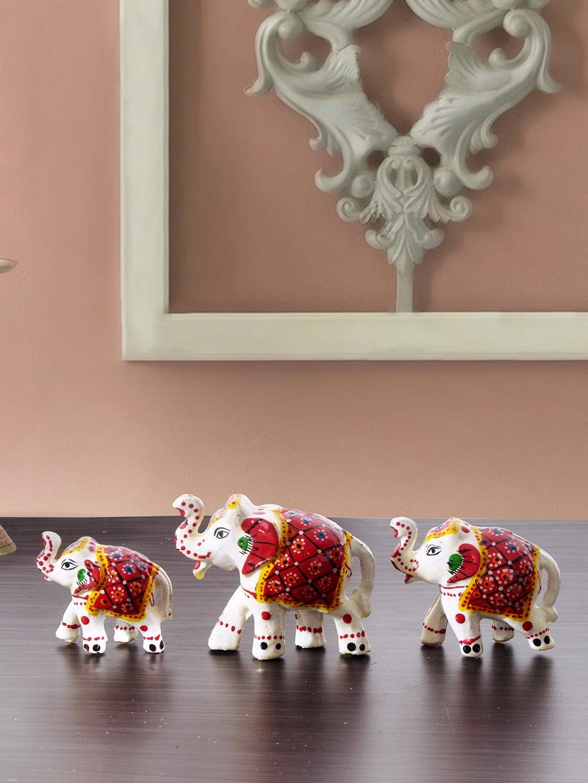 3 papier-mâché elephants on a table