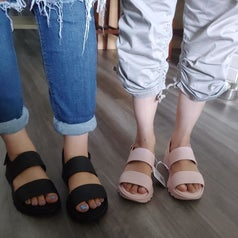 a reviewer image of two people wearing the same sandals in black and blush pink