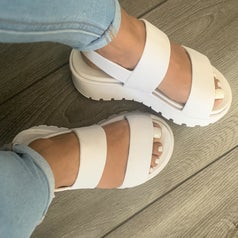 a reviewer image of someone wearing jeans and the slingback sandals in white