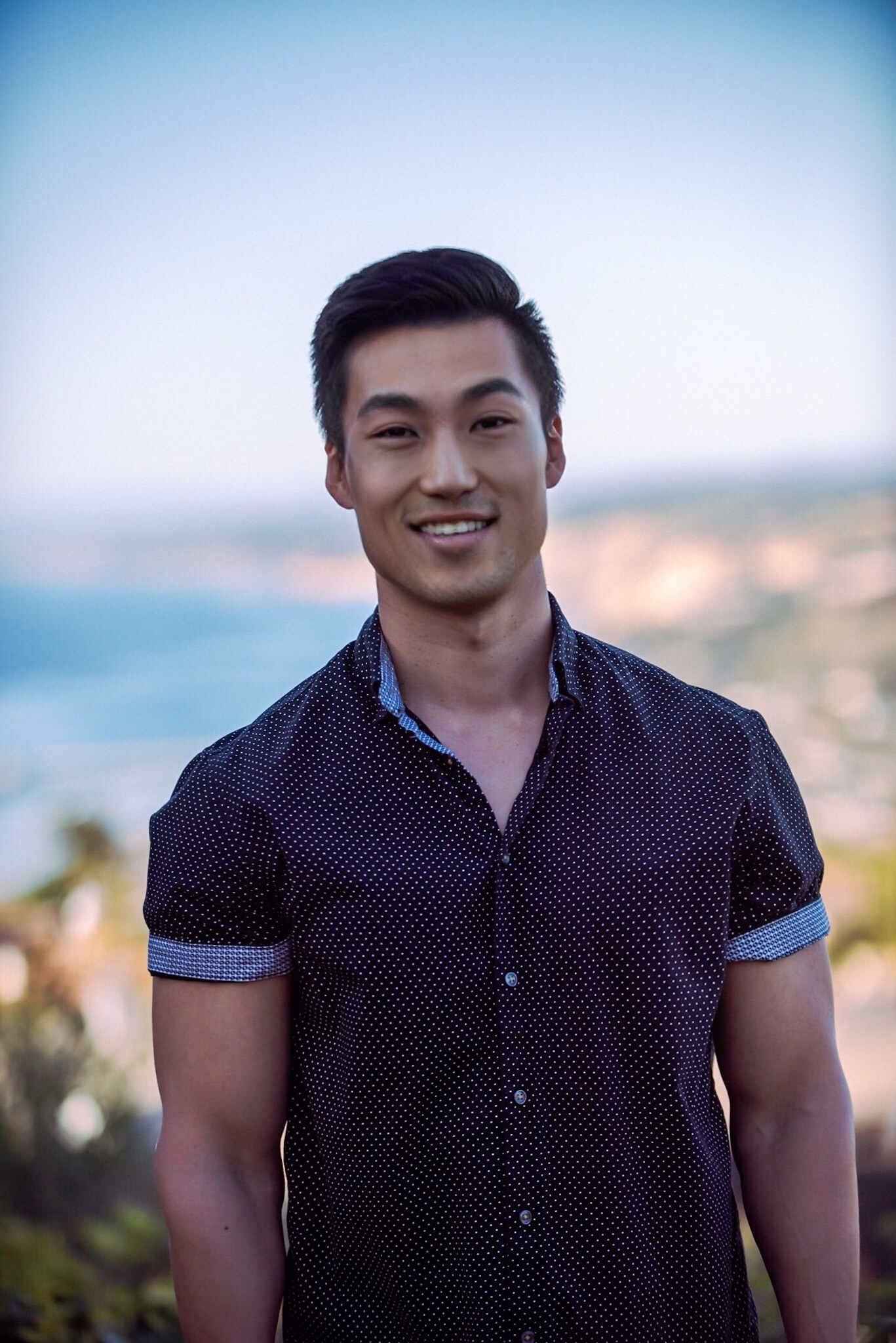 Bao smiling in a short-sleeved shirt and the beach behind him