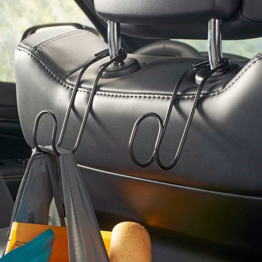 A pair of metal hooks on the back of a drivers' seat headrest