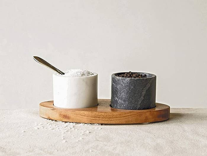 a black and white marble bowl resting on a wooden tray with salt and pepper in each bowl