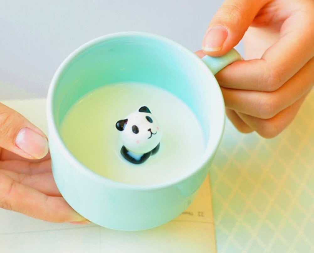 person holding the mug with a panda inside