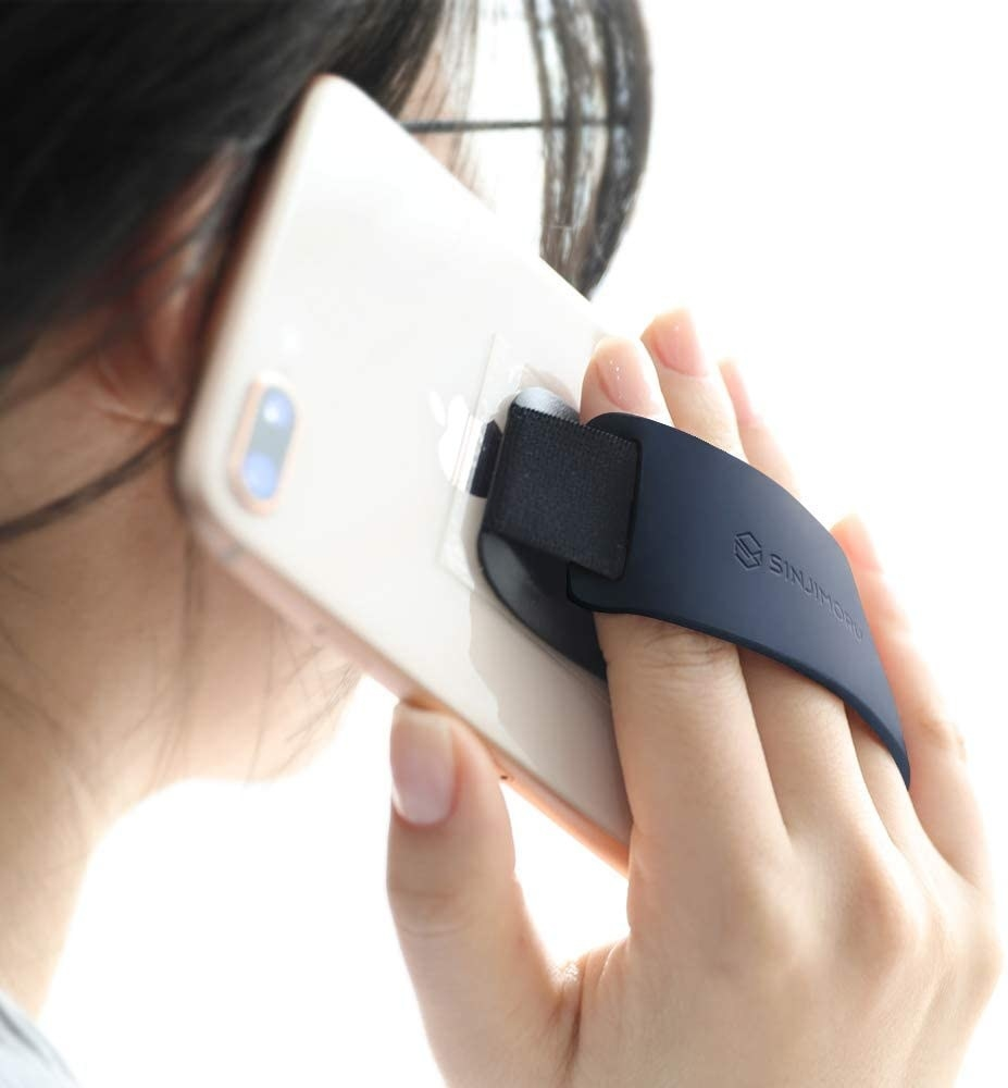 Someone holding up their phone while using the silicone grip
