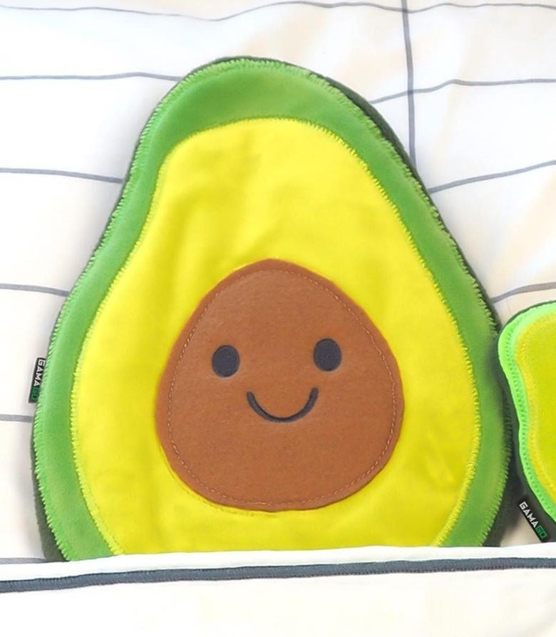 A smiling avocado-shaped heating pad