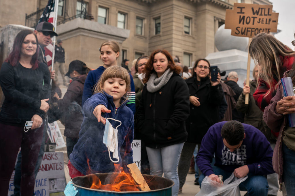 A crowd scene showing a young girl throwing a face mask into a garbage can that is on fire