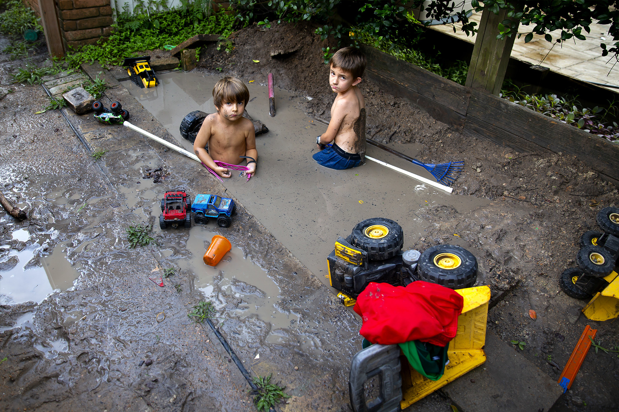 Two boys in a backyard mud pit