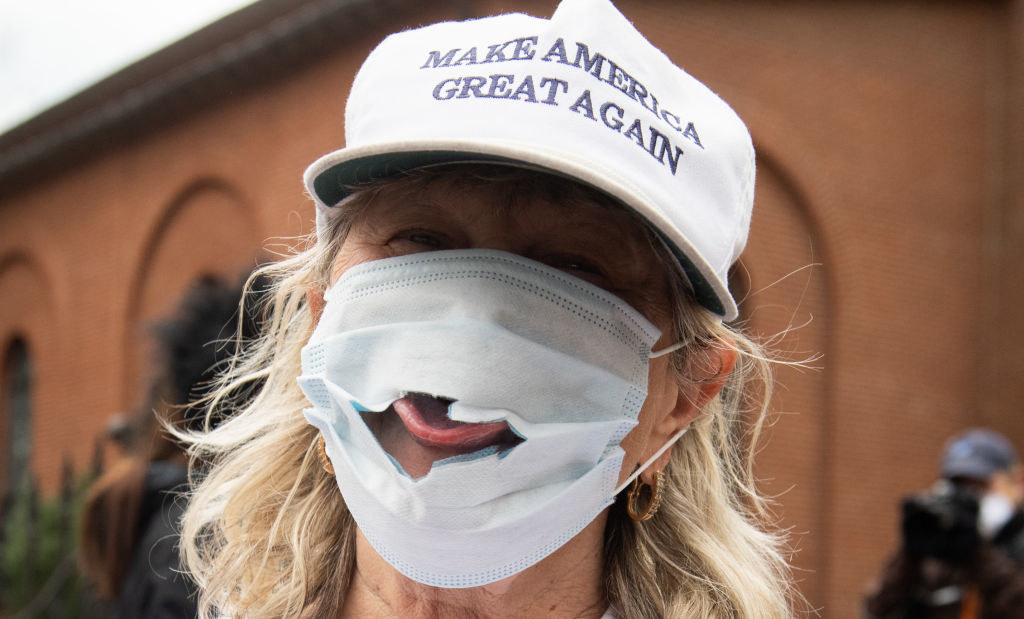 """Person wearing a """"Make America great again"""" hat and a face mask with a large hole by the mouth, showing their stuck-out tongue"""
