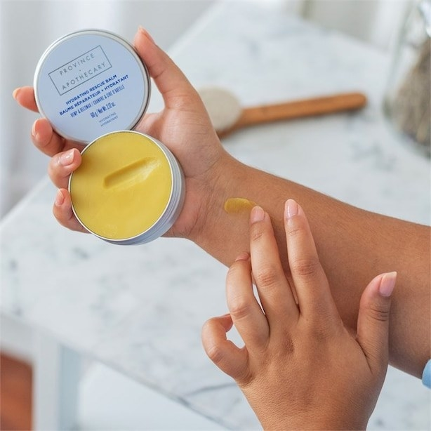 A person holding the tin of balm and applying some to their arm