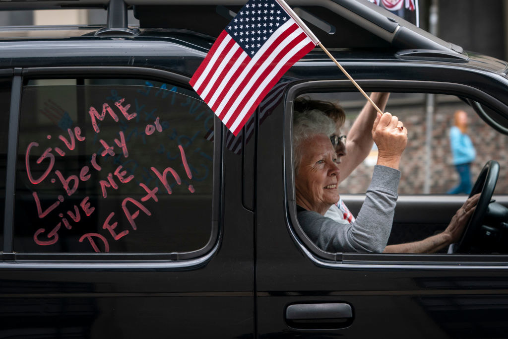 """Older woman in the passenger seat of a truck and waving an American flag with the words """"Give me liberty or give me death!"""" on the car window behind her"""