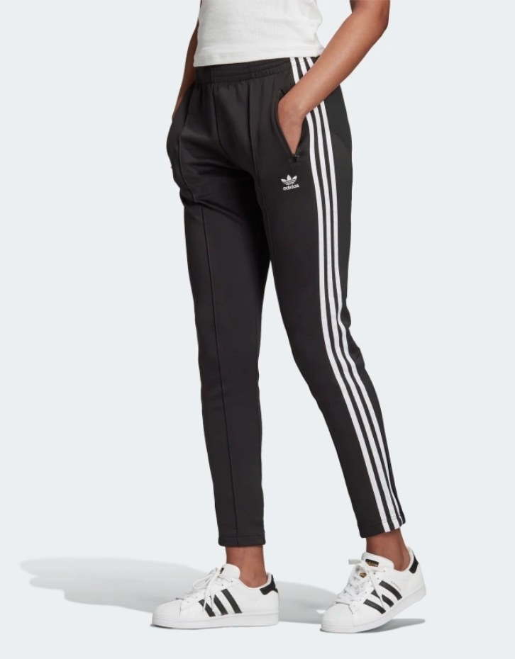 Model wearing black track pants with white stripes down the side