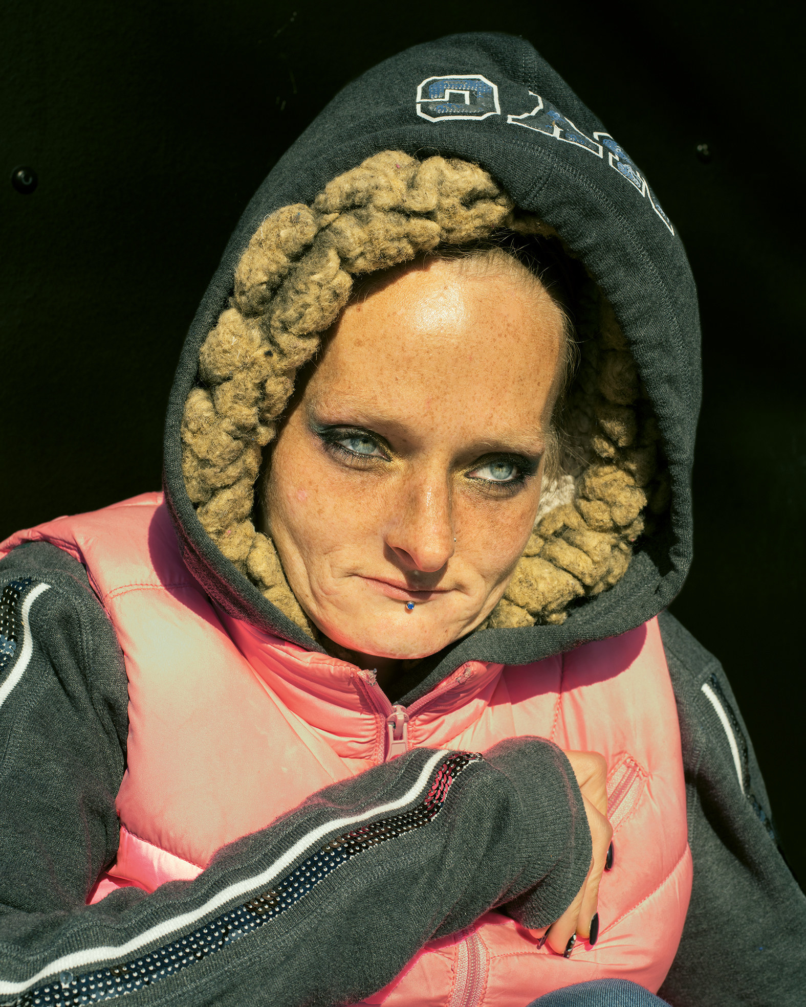 A woman in a hoodie and vest curls up into herself, looks out past the camera