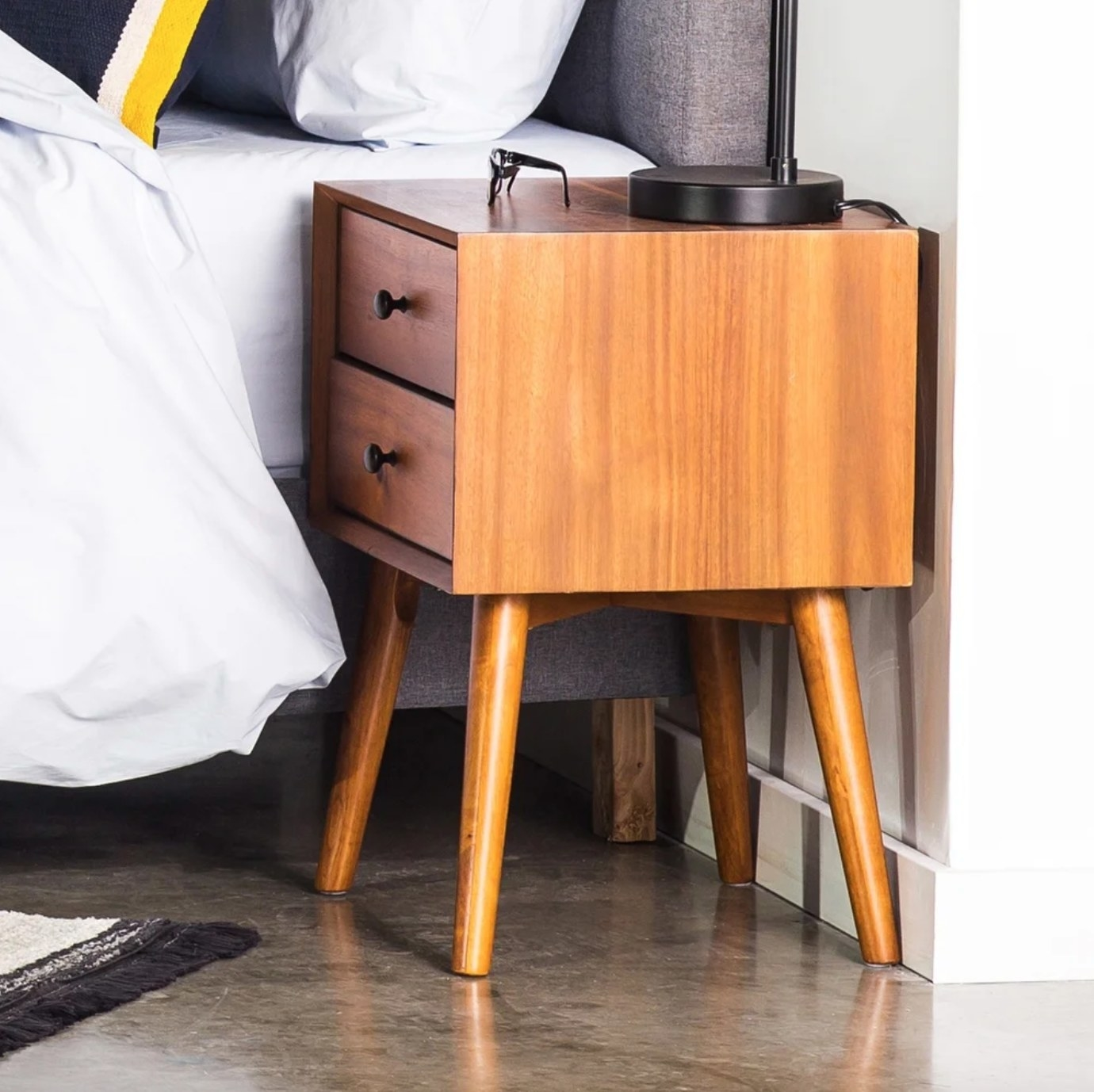 The acacia wood nightstand in a bedroom