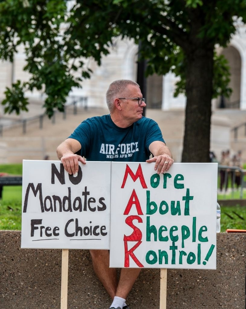"""Man in an Air Force T-shirt holding two signs, one reading, """"No Mandates Free Choice"""" and another reading, """"More About Sheeple Kontrol!"""" with the letters M-A-S-K highlighted"""
