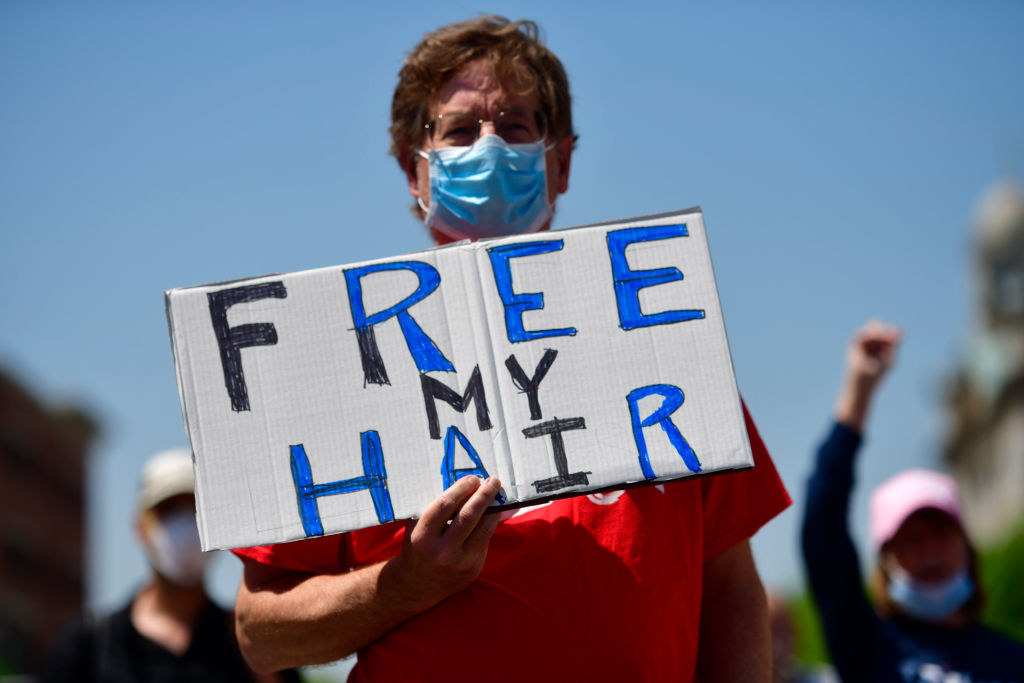 """Person holding a sign reading, """"Free my hair"""""""