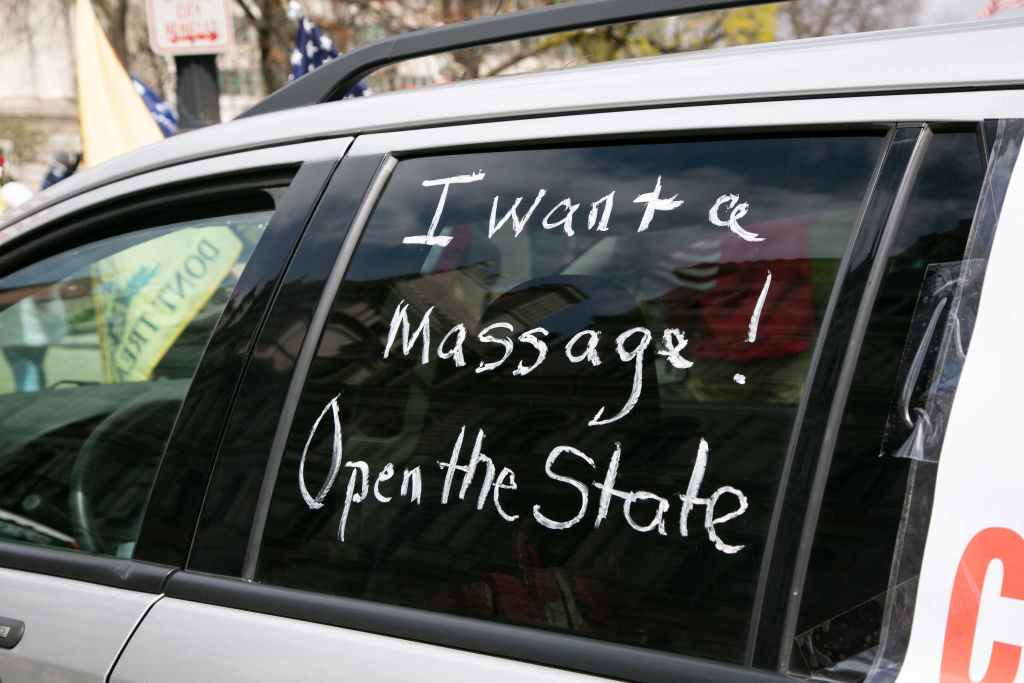 """A car window with the writing, """"I want a massage! Open the state"""""""