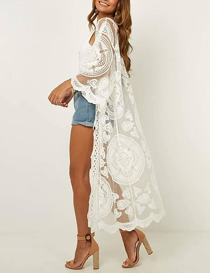 model wearing long white lacy duster with heels and denim shorts