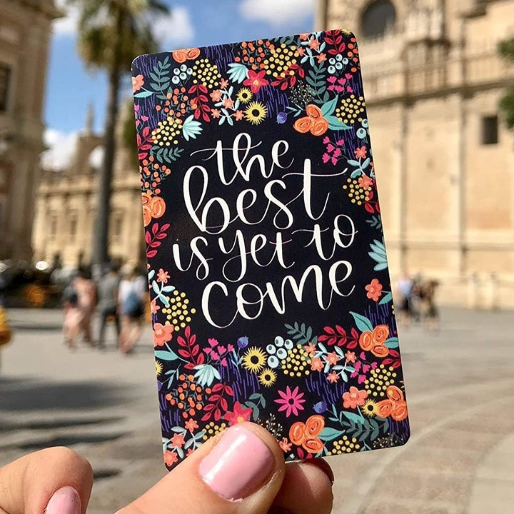 """the black card with the phrase """"the best is yet to come"""""""