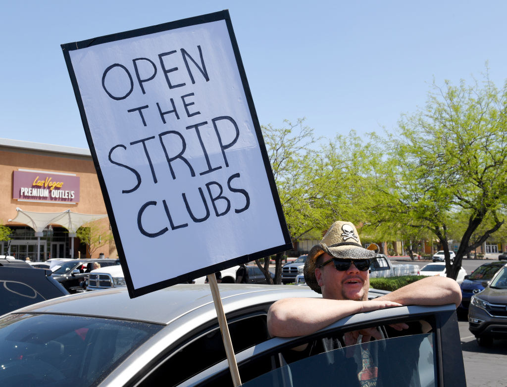 """Man standing outside his car with a sign reading, """"Open the strip clubs"""""""