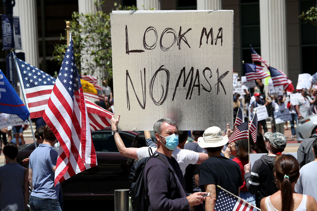 """Person in a crowd of protesters holding up a sign reading, """"Look Ma no mask"""""""
