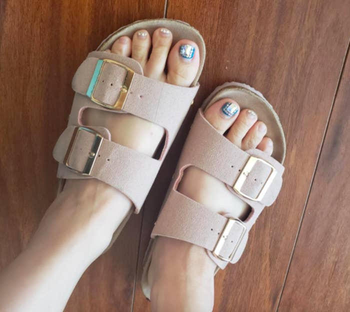 Reviewer wearing the Birkenstock-like sandals in beige
