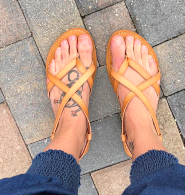 Reviewer wearing the strappy crisscross sandals in tan
