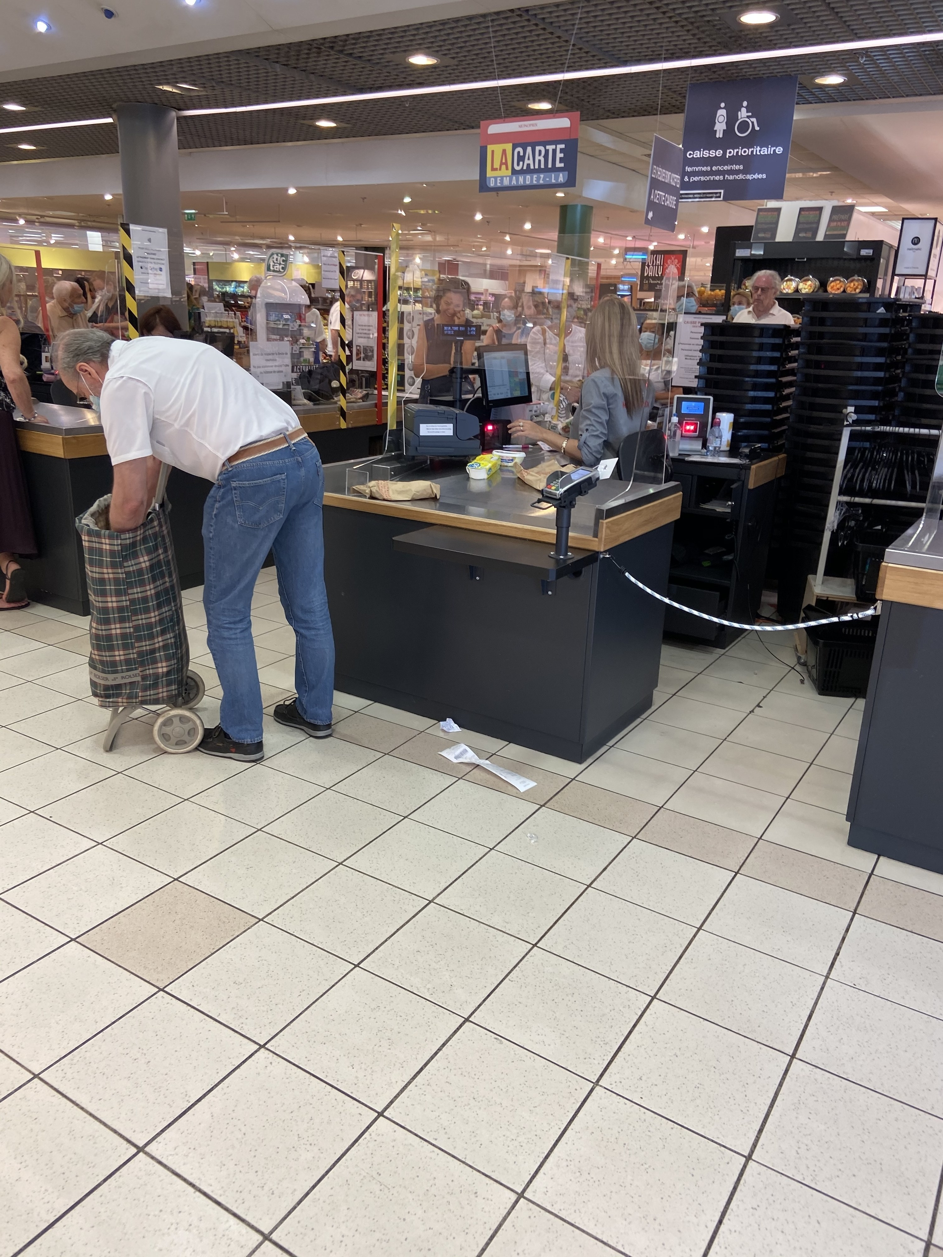 A man bagging his groceries at a supermarket in France
