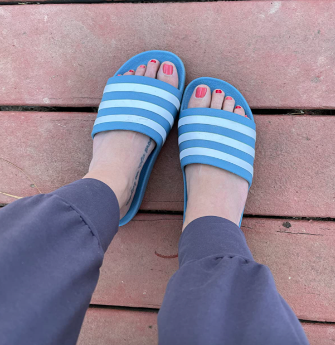 Reviewer wearing the blue and white striped Adidas sandals
