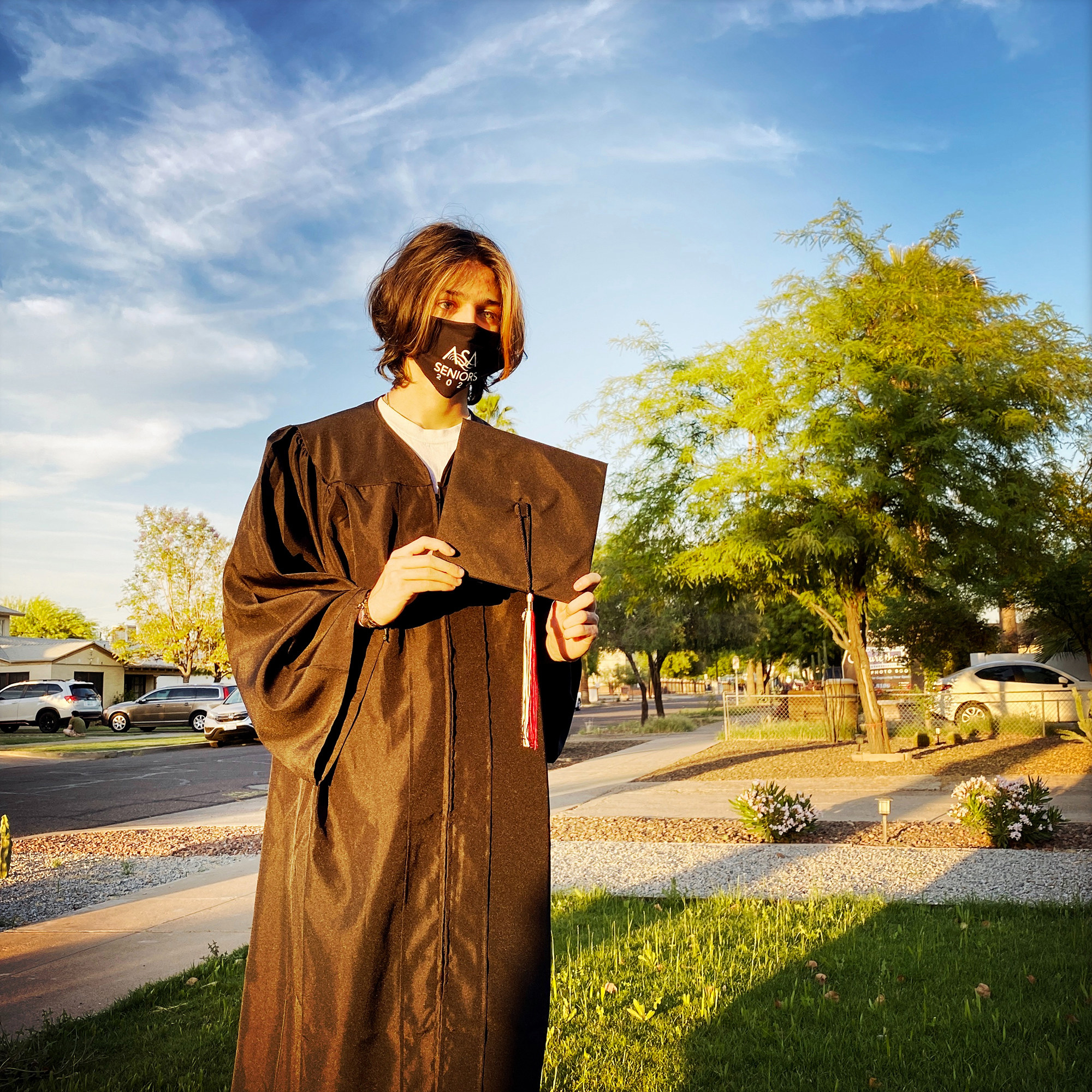 A teenager in a graduation cap and gown stands during sundown, casting a long shadow